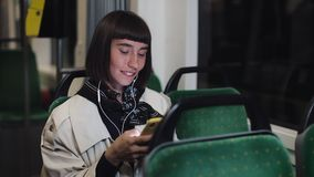 Portrait of young stylish woman with headphones listening to music, using smartphone, sing and funny dancing in public. Transport. City lights background stock footage
