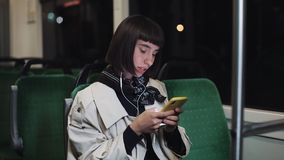 Portrait of young stylish woman with headphones listening to music, using smartphone, sing and funny dancing in public. Transport. City lights background stock video footage