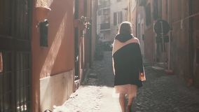 Portrait of young stylish woman walking in the alley, side street. Happy girl explores the old part of the city. Portrait of young stylish woman walking in then stock video