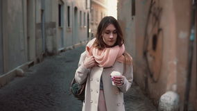 Portrait of young stylish woman walking in the city centre. Happy girl explores the old streets and drinking coffee. Portrait of young stylish woman walking in stock footage