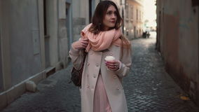 Portrait of young stylish woman walking in the city centre. Happy girl explores the old streets and drinking coffee. Royalty Free Stock Images