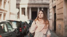 Portrait of young stylish woman walking in the city centre. Inspired and happy girl explores the old streets of the city. Early sunny morning in Europe stock video footage