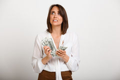 Portrait of young successful business woman over white backgroun. Portrait of young successful business woman counting money over white background Royalty Free Stock Images