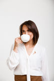 Portrait of young successful business woman over white backgroun. Portrait of young successful business woman, drinking coffee, over white background Royalty Free Stock Photography