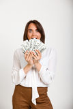 Portrait of young successful business woman over white backgroun. Portrait of young successful business woman holding money, looking at camera over white Royalty Free Stock Photo