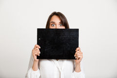 Portrait of young successful business woman over white backgroun. Portrait of young successful business woman looking at camera, holding folder over white Royalty Free Stock Photo