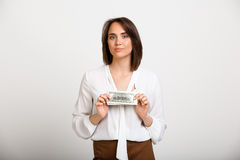 Portrait of young successful business woman over white backgroun. Portrait of young successful business woman looking at camera, holding money, over white Stock Image