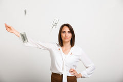 Portrait of young successful business woman over white backgroun. Portrait of young successful business woman looking at camera, throw up money, over white Royalty Free Stock Photo