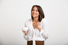 Portrait of young successful business woman over white backgroun. Portrait of young successful business woman, smiling, gesturing, holding cup of coffee, over Stock Photography