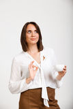 Portrait of young successful business woman over white backgroun. Portrait of young successful business woman, smiling, holding cup of coffee, showing okay, over Royalty Free Stock Image