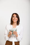 Portrait of young successful business woman over white backgroun. Portrait of young successful business woman smiling, holding money, over white background Stock Photography