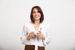 Portrait of young successful business woman over white backgroun. Portrait of young successful business woman, smiling, looking at camera, holding cup of coffee Stock Photography