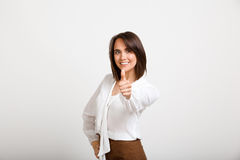 Portrait of young successful business woman over white backgroun. Portrait of young successful business woman smiling, showing thumb up, looking at camera, over Royalty Free Stock Photo