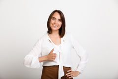Portrait of young successful business woman over white backgroun. Portrait of young successful business woman smiling, showing thumb up, looking at camera, over Stock Photo