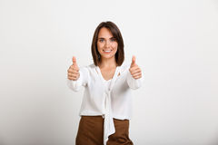 Portrait of young successful business woman over white backgroun. Portrait of young successful business woman smiling, showing thumbs up, looking at camera, over Royalty Free Stock Image
