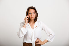 Portrait of young successful business woman over white backgroun. Portrait of young successful business woman solving problems on phone over white background Royalty Free Stock Photo