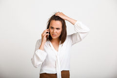 Portrait of young successful business woman over white backgroun. Portrait of young successful business woman solving problems on phone over white background Stock Photo