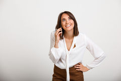 Portrait of young successful business woman over white backgroun. Portrait of young successful business woman speaking on phone, smiling over white background Stock Photo
