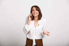 Portrait of young successful business woman over white backgroun. Portrait of young successful business woman speaking on phone, smiling over white background Royalty Free Stock Image