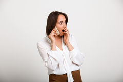 Portrait of young successful business woman over white backgroun. Portrait of young successful business woman speaking on phone, surprised, over white background Stock Image