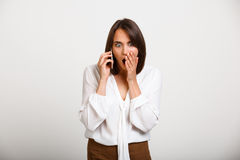 Portrait of young successful business woman over white backgroun. Portrait of young successful business woman speaking on phone, surprised, over white background Stock Photos