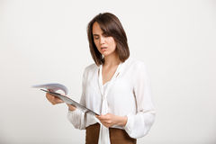 Portrait of young successful business woman over white backgroun. Portrait of surprised young successful business woman checking papers over white background Royalty Free Stock Photography