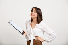Portrait of young successful business woman over white backgroun. Portrait of surprised young successful business woman checking papers over white background Royalty Free Stock Image