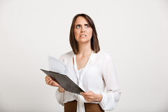 Portrait of young successful business woman over white backgroun. Portrait of surprised young successful business woman checking papers over white background Royalty Free Stock Images