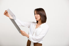Portrait of young successful business woman over white backgroun. Portrait of surprised young successful business woman checking papers over white background Stock Photos