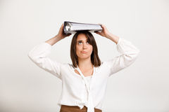 Portrait of young successful business woman over white backgroun. Portrait of upset young successful business woman with folder on head over white background Stock Photos