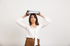 Portrait of young successful business woman over white backgroun. Portrait of upset young successful business woman with folder on head over white background Stock Image