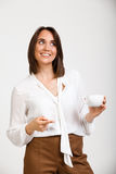 Portrait of young successful business woman over white background. Portrait of young successful business woman, smiling, holding cup of coffee, over white Stock Images