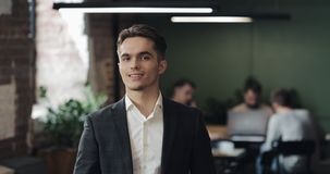 Portrait of young successful businessman at busy office. Handsome male employee looking at camera and smiling. Business stock footage