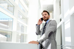 Portrait of a young successful businessman speaking on the mobile phone while standing in the modern office interior Stock Photo