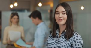 Portrait of young successful businesswoman looking at camera standing in office workspace. Working people on the blurred