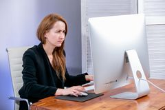 Portrait of young successful businesswoman at office. She sits at the table and sadly looks at the display, office work. Black Fri stock photo