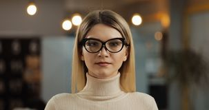 Portrait of young successful businesswoman wearing stylish glasses looking at camera standing in office workspace. stock photo