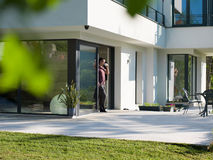Man drinking coffee in front of her luxury home villa. Portrait of a young successful man drinking coffee in the doorway of his luxury home villa royalty free stock images