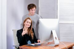 Portrait of young successful woman and man at office. They look at the display approvingly. Black Friday or Cyber Monday. Browsing royalty free stock photography