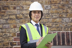 Portrait of young supervisor holding clipboard at construction site Royalty Free Stock Images
