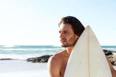 Portrait of young surfer at the beach. Close up side portrait of serious young surfer at the beach Stock Photography
