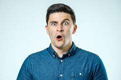 Portrait of young surprised man with opened mouth. Isolated on gray Stock Photo