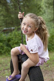 Portrait of young swinging on tire Stock Image