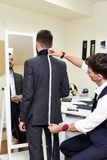 Tailor Measuring Model in Atelier. Portrait of young tailor measuring back of handsome men fitting bespoke suit in traditional atelier studio stock photos