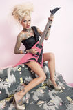 Portrait of young tattooed woman making faces while playing guitar Stock Images