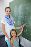 Portrait of young teacher assisting girl writing on chalkboard Stock Photos