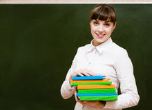 Portrait of young teacher with books. looking at camera Royalty Free Stock Image