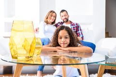Teenage girl with her family. Portrait of a young teenage african girl leaning on a coffee table while her family siting on a coach behind herr stock photography