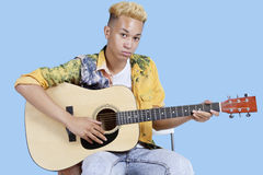 Portrait of a young teenage boy playing guitar over blue background Royalty Free Stock Photos
