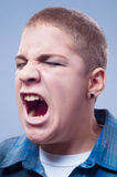 Portrait of young teenage boy screaming Stock Photos